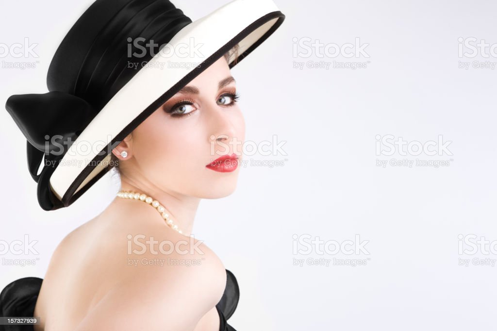 Beautiful Young Woman as Chanel Girl in Hat and Pearls stock photo