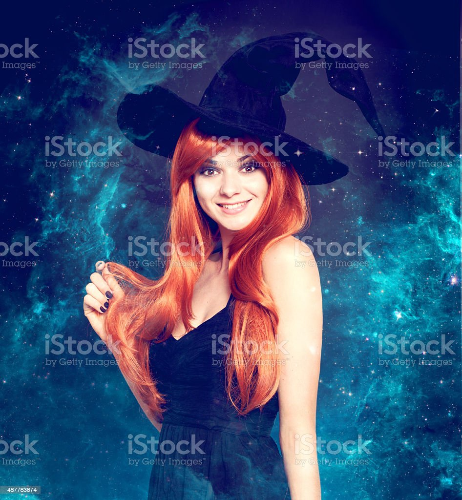 Beautiful young woman as halloween witch stock photo