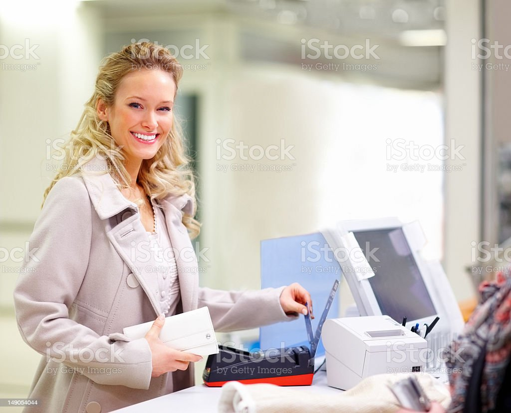 Beautiful young woman at cash counter in mall royalty-free stock photo