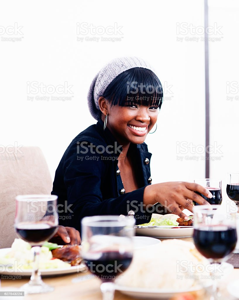 Beautiful young woman at dining table holding wine glass smiles stock photo