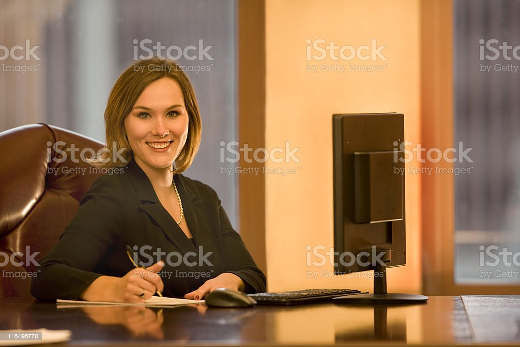 Beautiful Young Woman at Her Desk royalty-free stock photo