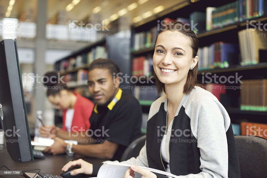 Beautiful young woman at library doing online research stock photo