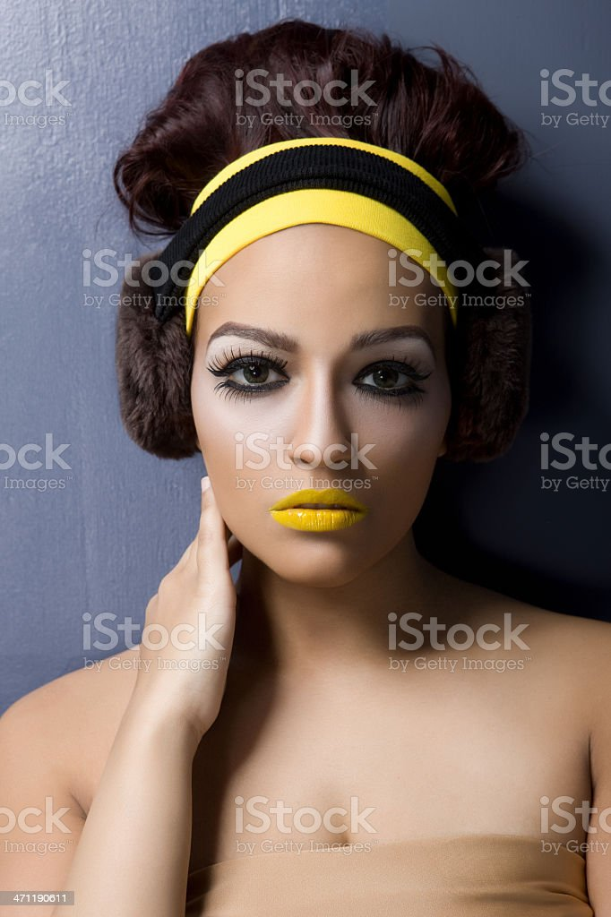 Beautiful Young Woman Beauty Model in 60s Makeup and Earmuffs royalty-free stock photo