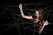 Beautiful young woman behind the net of ropes