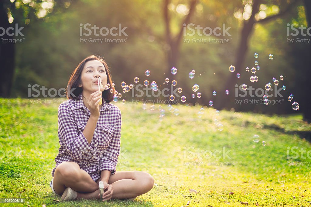 beautiful young woman blowing bubble stock photo