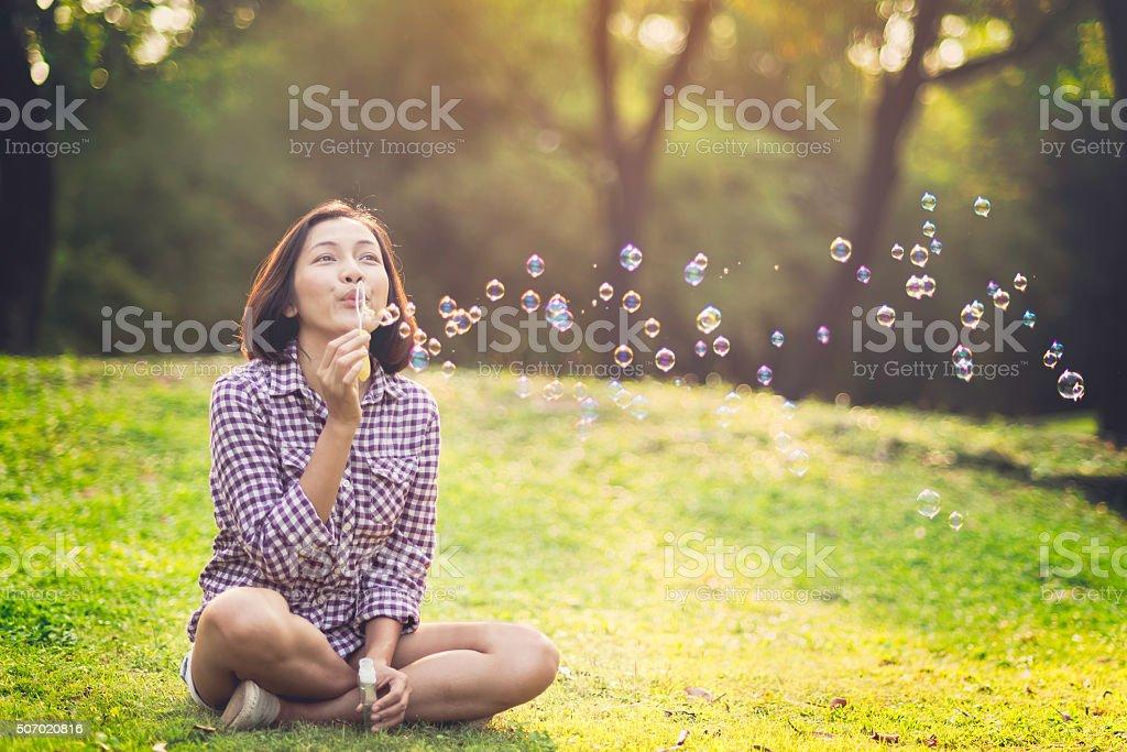 beautiful young woman blowing bubble stock photo
