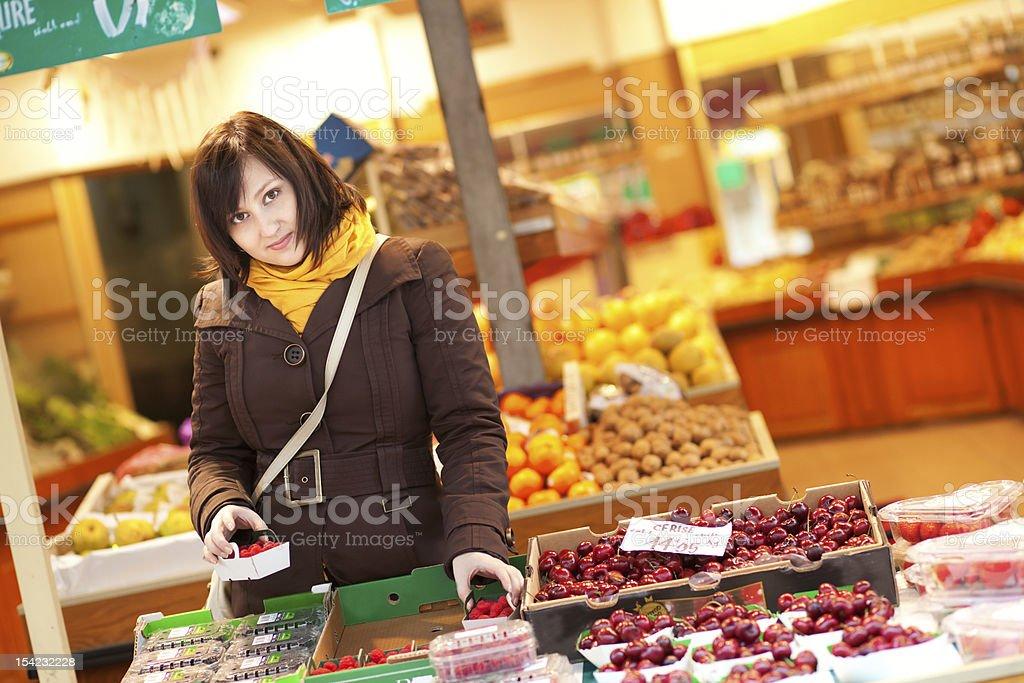 Beautiful young woman buying fruits at market royalty-free stock photo