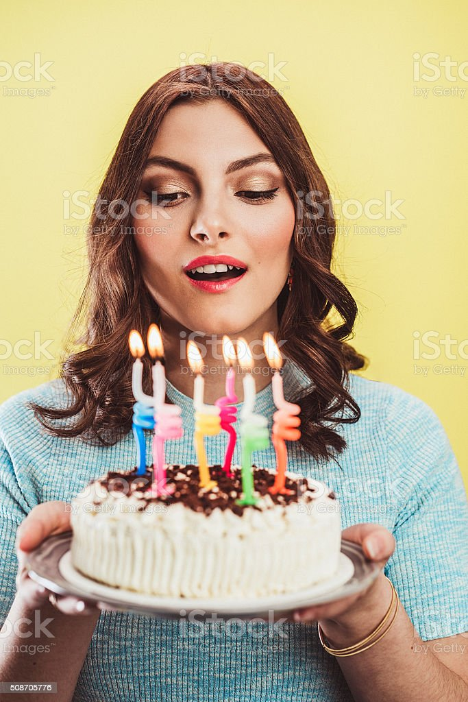 Beautiful young woman celebrating birthday with cake stock photo