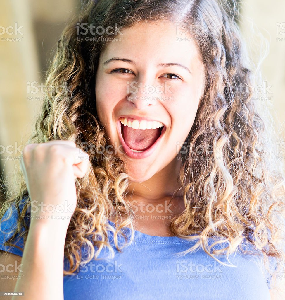 Beautiful young woman cheers, waving clenched fist stock photo