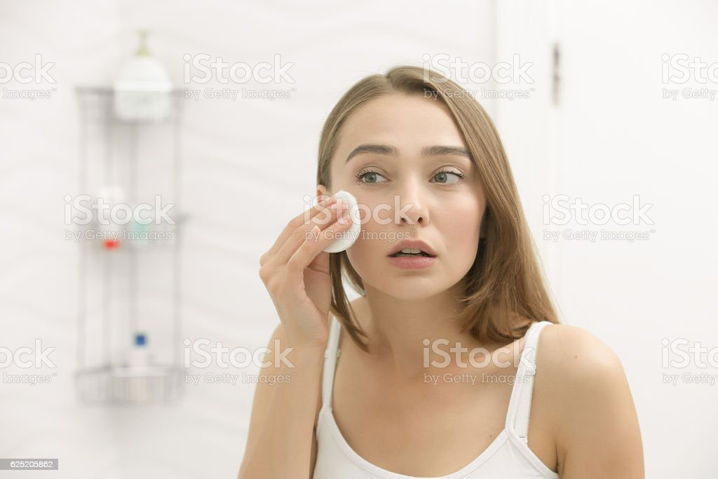 Beautiful young woman cleaning her skin with a cotton pad stock photo