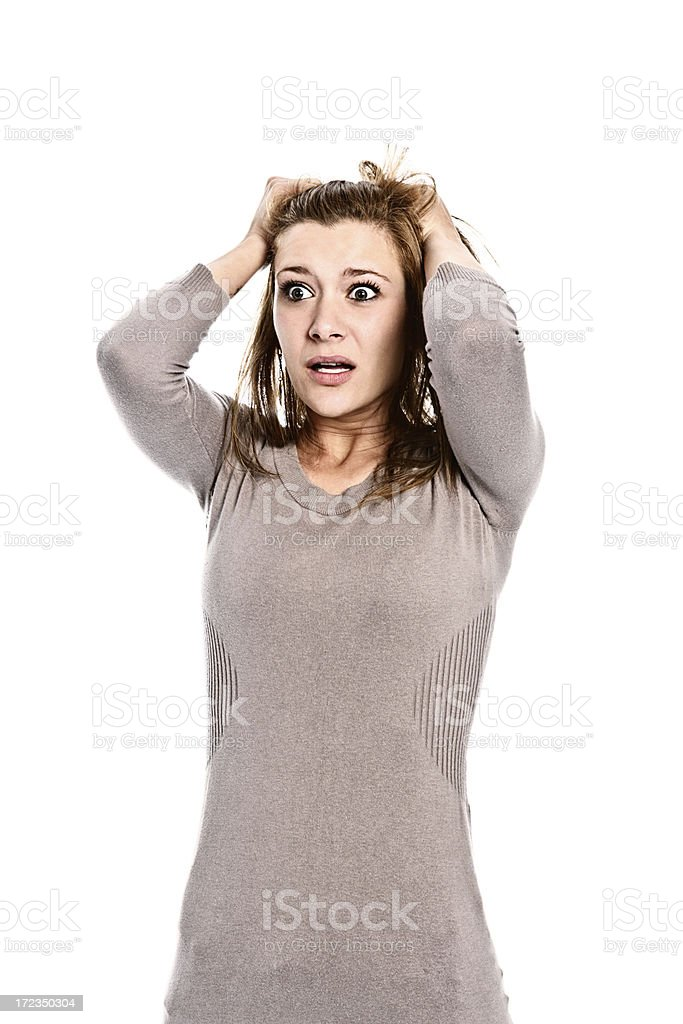 Beautiful young woman clutches her head in nervous horror royalty-free stock photo