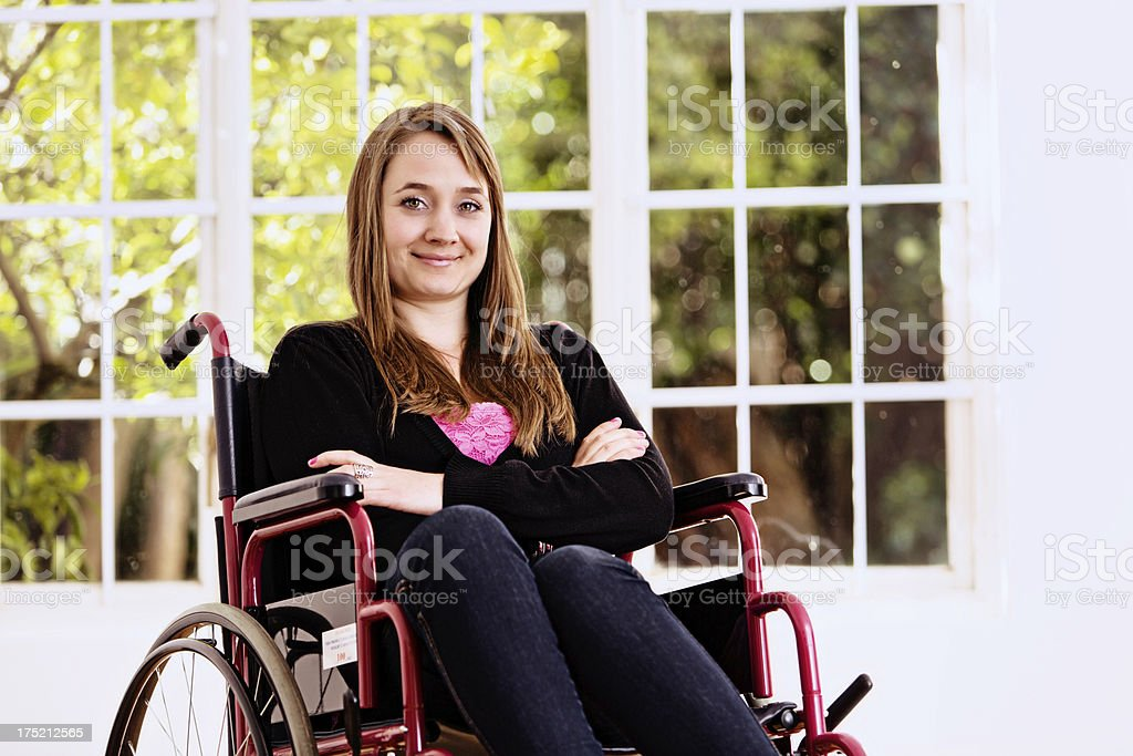 Beautiful young woman confined to wheelchair smiles bravely stock photo