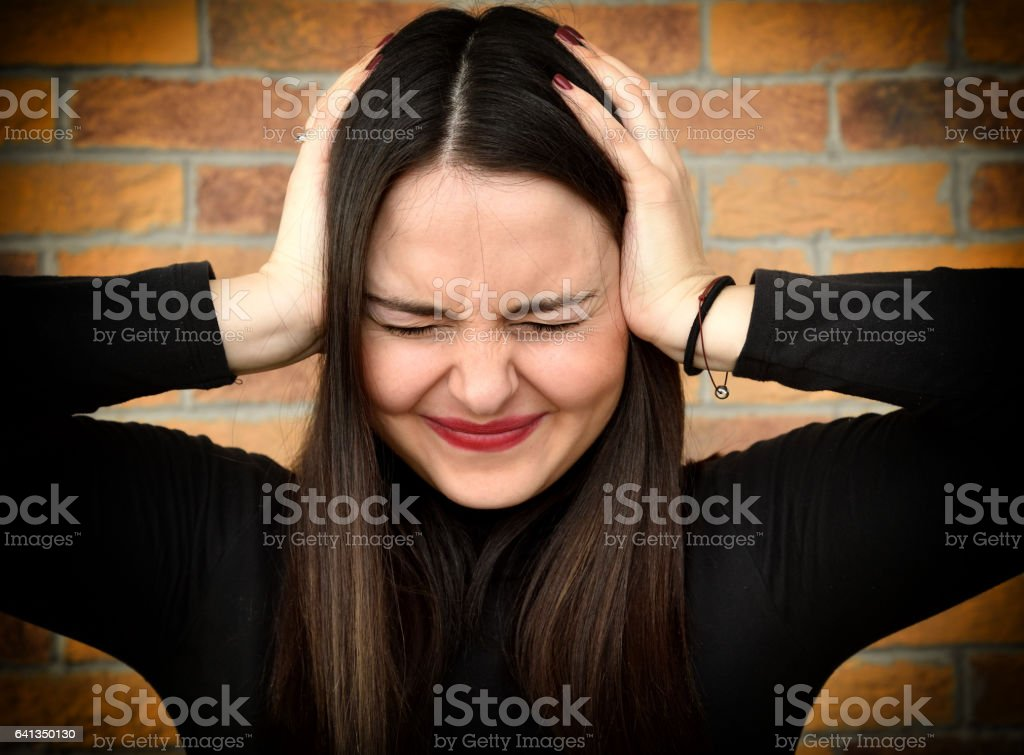Beautiful young woman covering her ears with hands stock photo