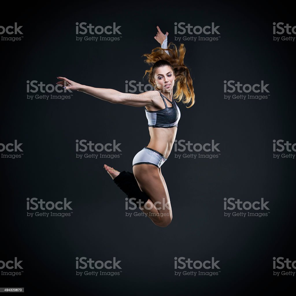Beautiful young woman dancer jumping in studio stock photo