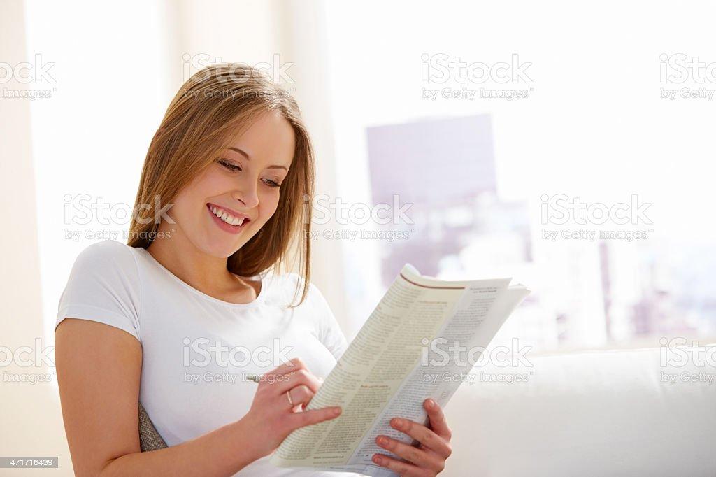 Beautiful young woman doing crossword - Indoors stock photo