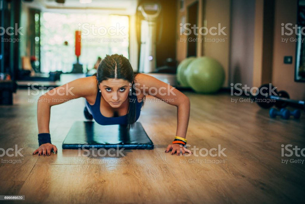 Beautiful young woman doing exercise at the gym stock photo