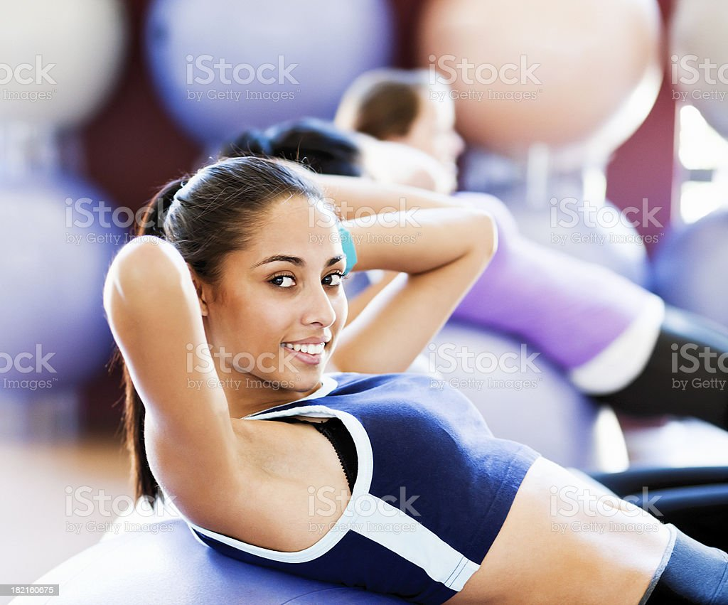 Beautiful young woman doing sit-ups smiles stock photo
