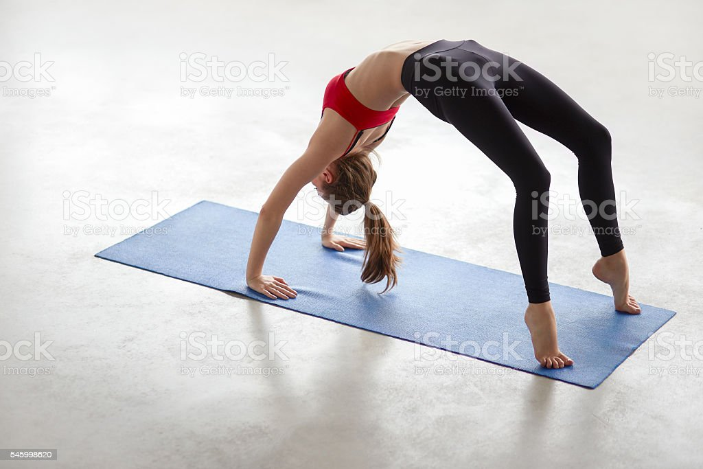 Beautiful young woman doing yoga exercise Bridge Pose stock photo