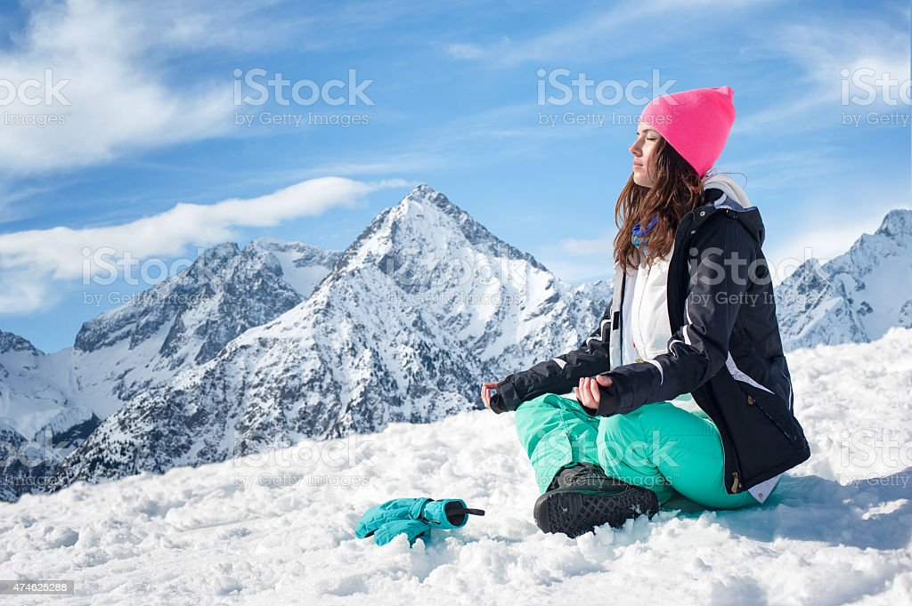 Beautiful young woman doing yoga in the snow mountains stock photo