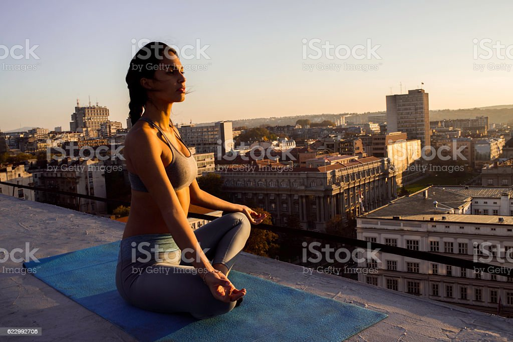 beautiful young woman doing yoga on the rooftop stock photo