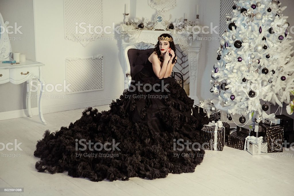 beautiful young woman dressed in a luxurious black dress stock photo