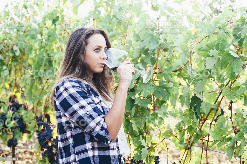 Beautiful young woman drinking a glass in row of vineyard stock photo