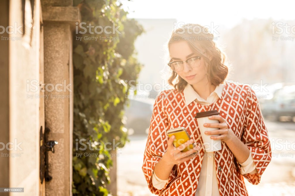 Beautiful young woman drinking coffee from takeaway cup in the morning. stock photo