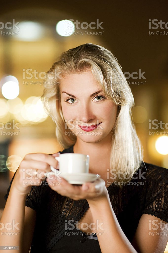 Beautiful young woman drinking coffee in a restaurant royalty-free stock photo