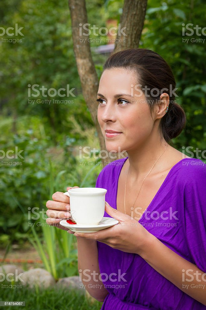 Beautiful young woman drinking coffee outdoors stock photo