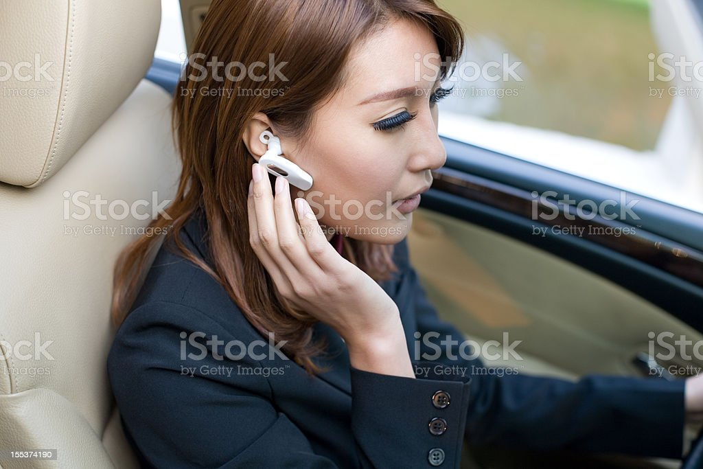 Beautiful Young Woman Driving  Car Talking on Bluetooth Headset stock photo