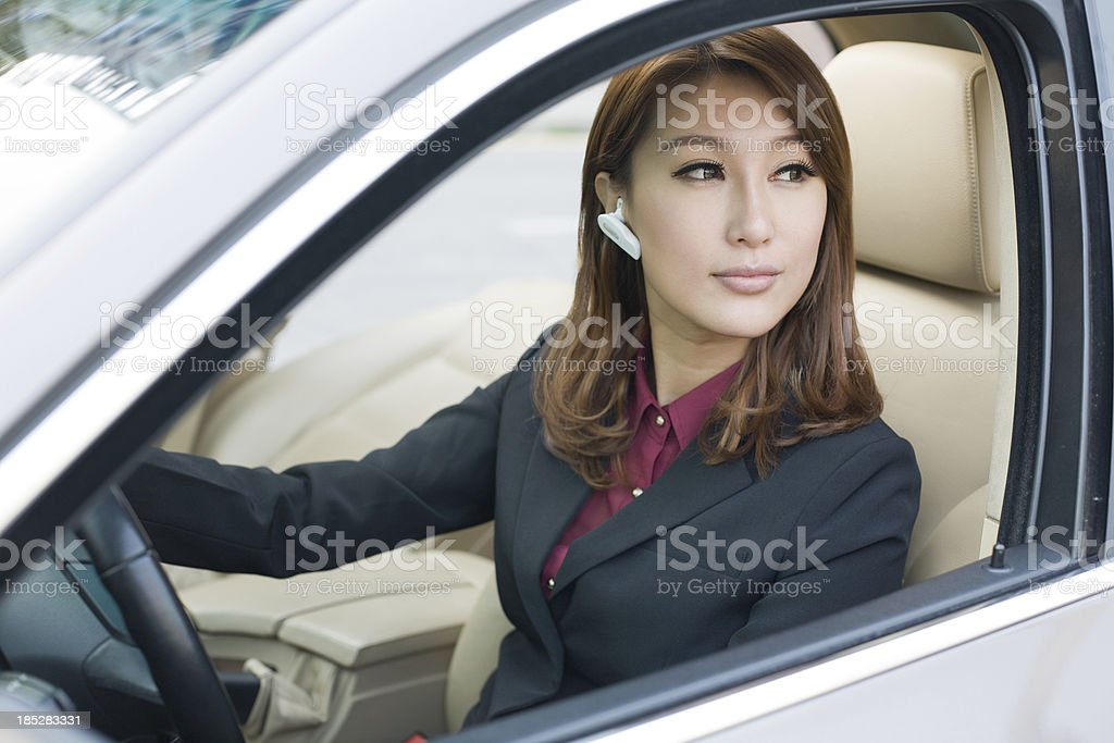 Beautiful Young Woman Driving  Car Talking on Bluetooth Headset royalty-free stock photo