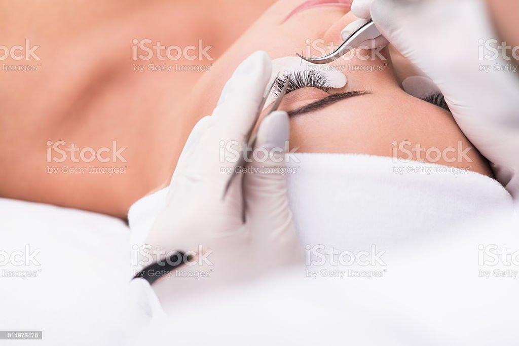 Beautiful young woman during eyelash extension stock photo