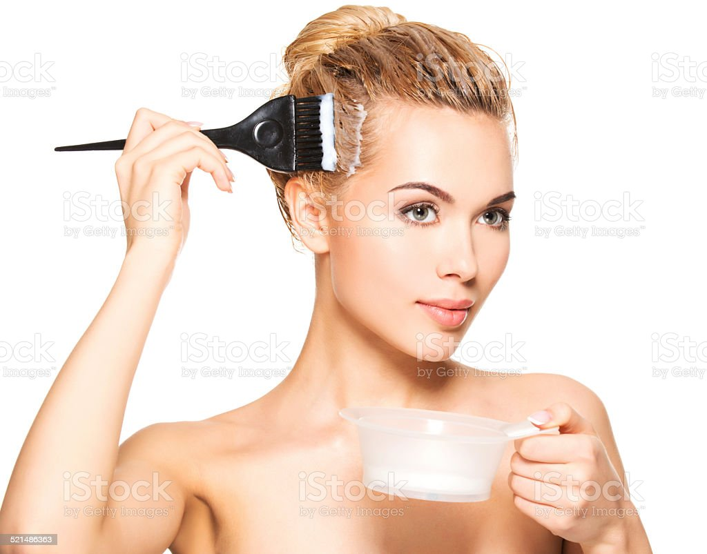 Beautiful young woman dyes her hair stock photo