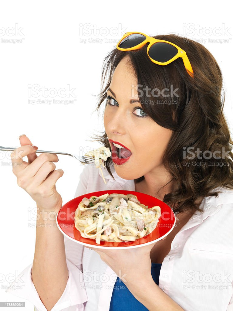 Beautiful Young Woman Eating a Creamy Carbonara Pasta stock photo