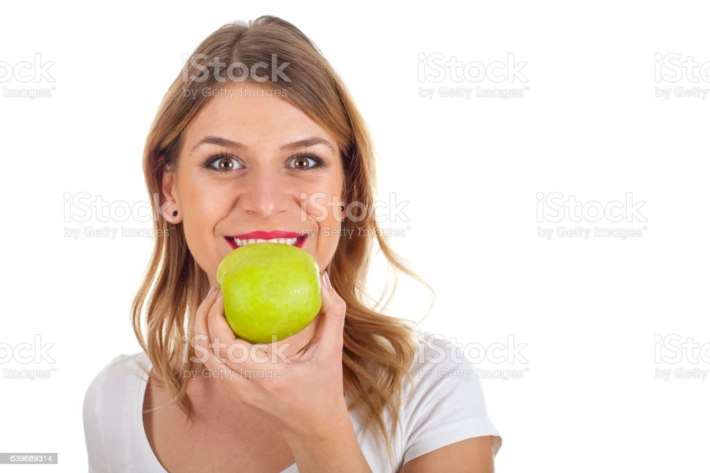 Beautiful young woman eating an apple stock photo