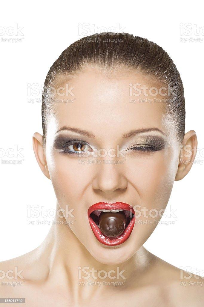 Beautiful young woman eating chocolates royalty-free stock photo
