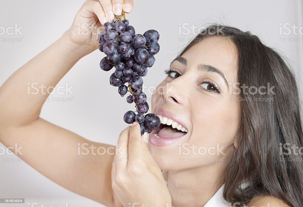 Beautiful young woman eating grapes royalty-free stock photo
