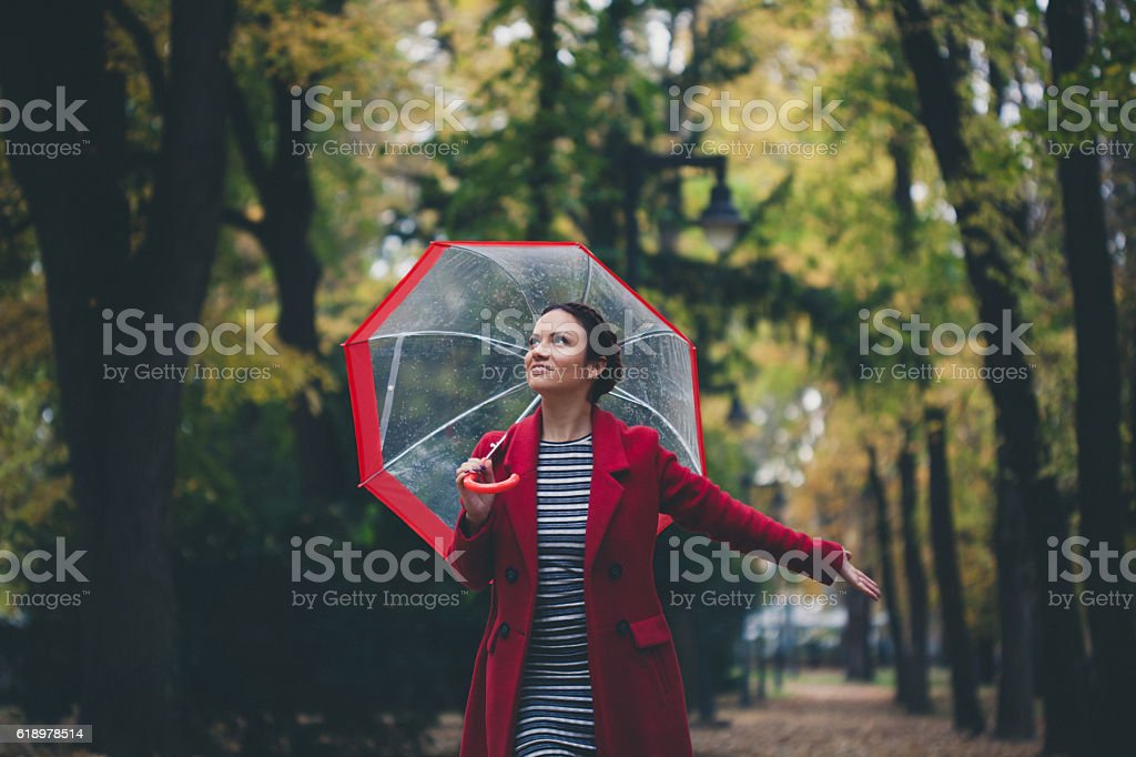 Beautiful young woman enjoying a rainy day stock photo