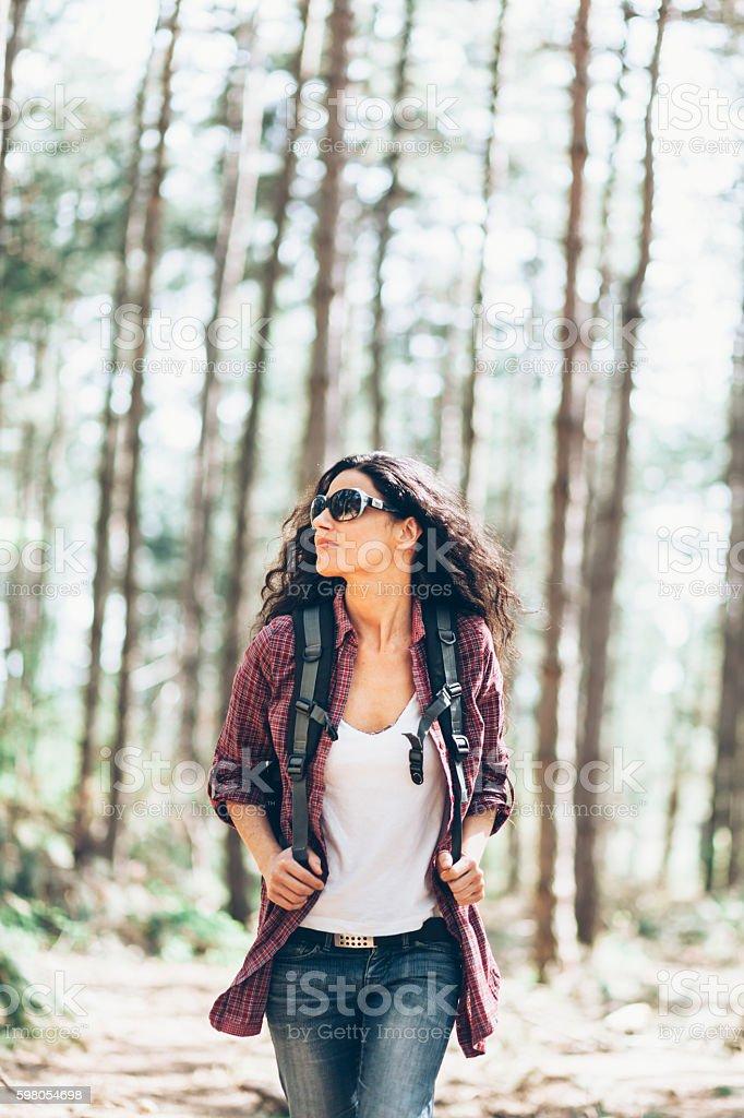 Beautiful young woman enjoying forest hiking stock photo
