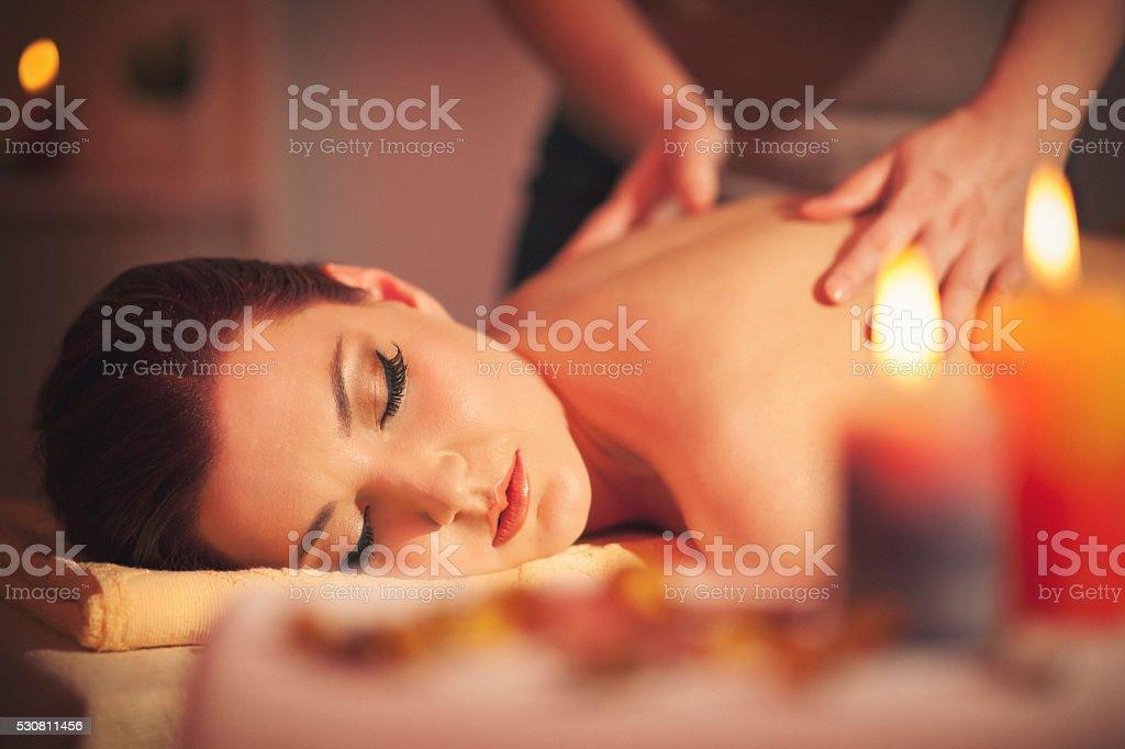 Beautiful young woman enjoying massage stock photo