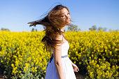 Beautiful young woman enjoying spring in a field.