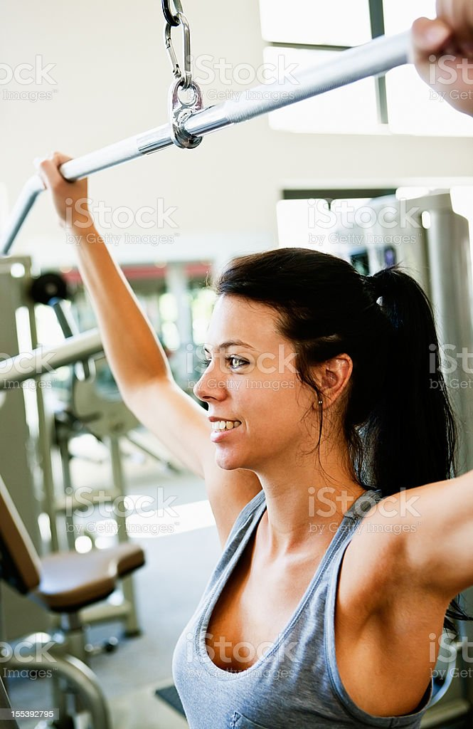 Beautiful young woman exercises arm and back muscles in gym stock photo