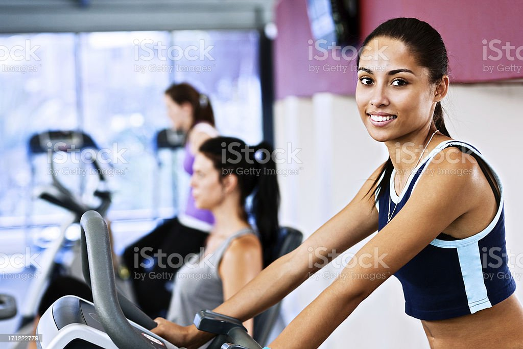 Beautiful young woman exercising in gym stock photo
