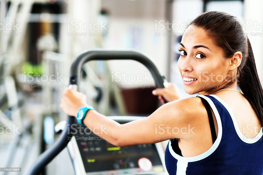 Beautiful young woman exercising in gym smiles over her shoulder stock photo
