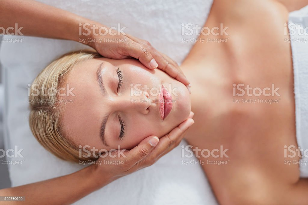 Beautiful young woman getting a facial massage stock photo