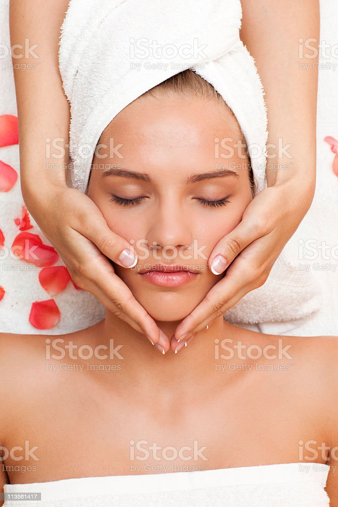 Beautiful young woman getting face massage from female hands royalty-free stock photo
