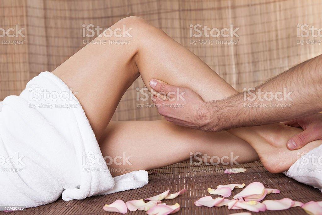 Beautiful young woman getting feet massage royalty-free stock photo