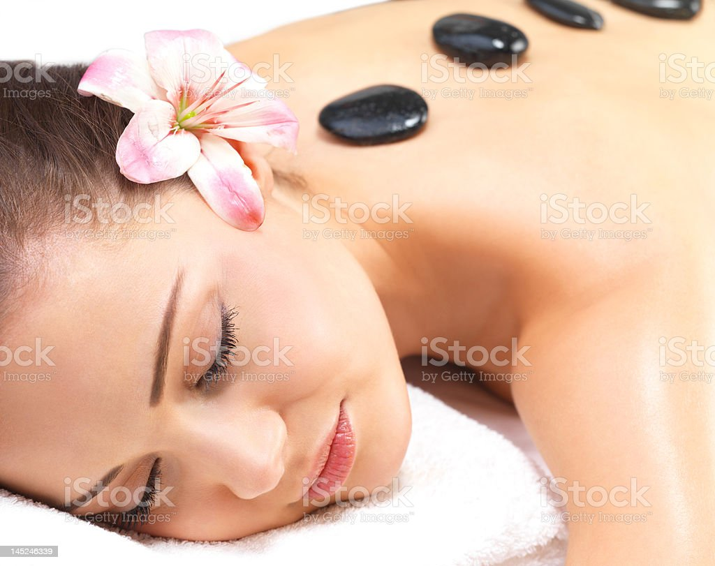 Beautiful young woman getting hot stone massage royalty-free stock photo