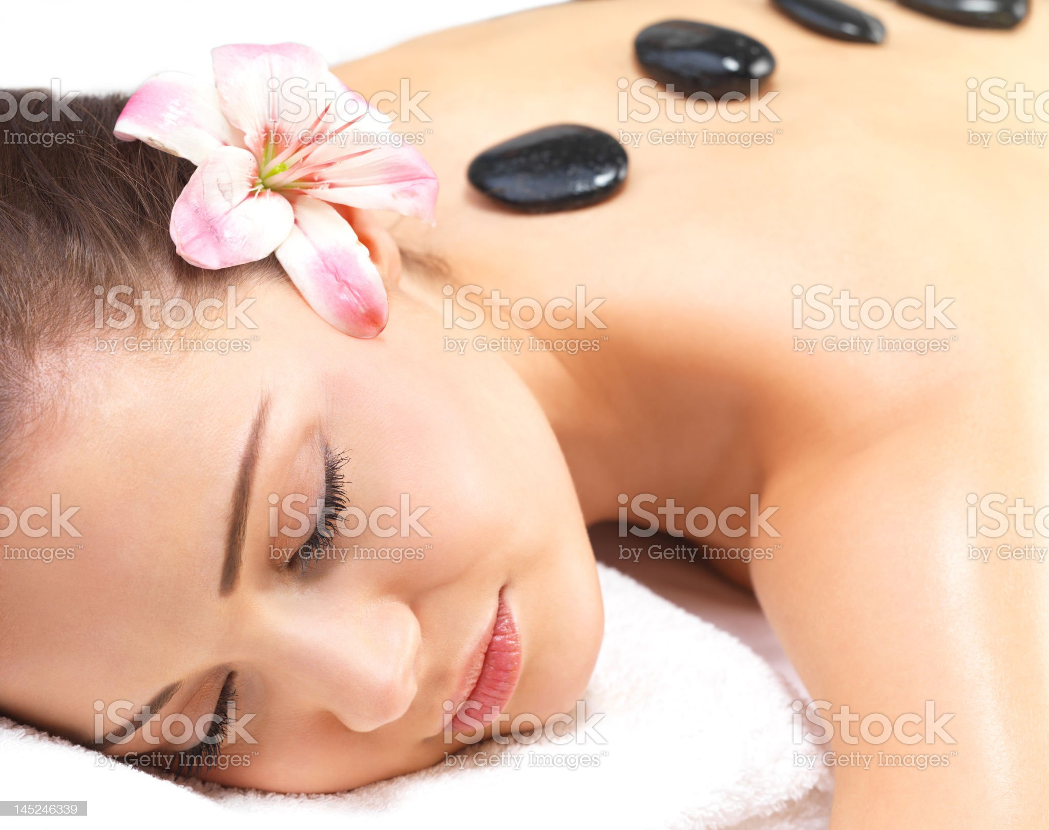 Beautiful young woman getting hot stone massage royalty-free stock photo