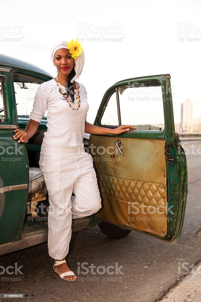 Beautiful young woman getting out of vintage car, Havana, Cuba stock photo